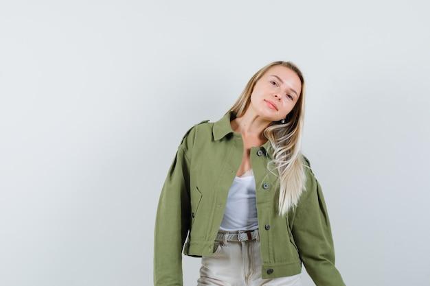 ジャケット、パンツに立って魅惑的に見ながらポーズをとる若い女性。正面図。