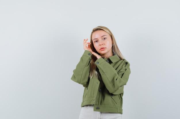 Молодая дама позирует, стоя в куртке, штанах и выглядит нежной, вид спереди.