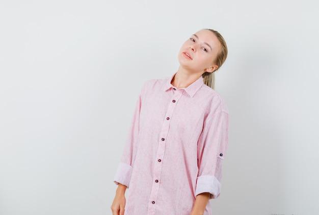 ピンクのシャツに立って誘惑しながらポーズをとる若い女性