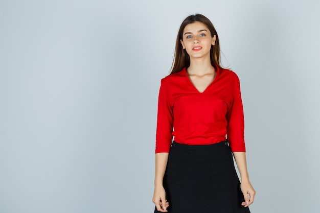Молодая дама позирует, стоя в красной блузке, юбке и нежно выглядит