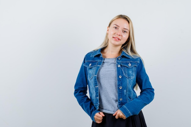 T- 셔츠, 데님 재킷, 스커트에 서 있고 매혹적인 찾고있는 동안 포즈를 취하는 젊은 아가씨.
