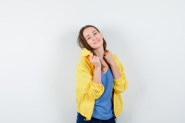 Giovane donna in posa mentre è in piedi in maglietta, giacca e sembra stupenda