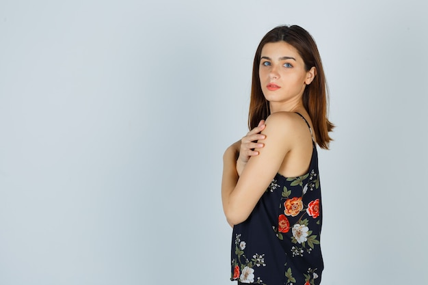 Giovane donna in posa mentre si tocca il braccio in camicetta e sembra aggraziata. .