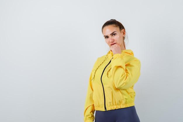 Молодая дама позирует с рукой на подбородке в желтой куртке и выглядит привлекательно. передний план.