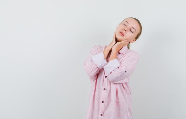 Giovane donna in posa con gli occhi chiusi in camicia rosa e dall'aspetto seducente