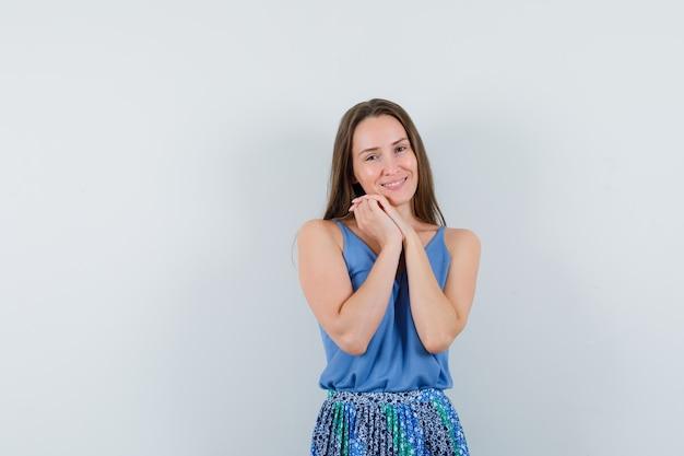 ブラウス、スカート、感情的に見える胸に手を組み合わせてポーズをとる若い女性。正面図。