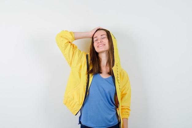 Giovane signora in posa con la mano sulla testa e guardando fiduciosa. vista frontale.