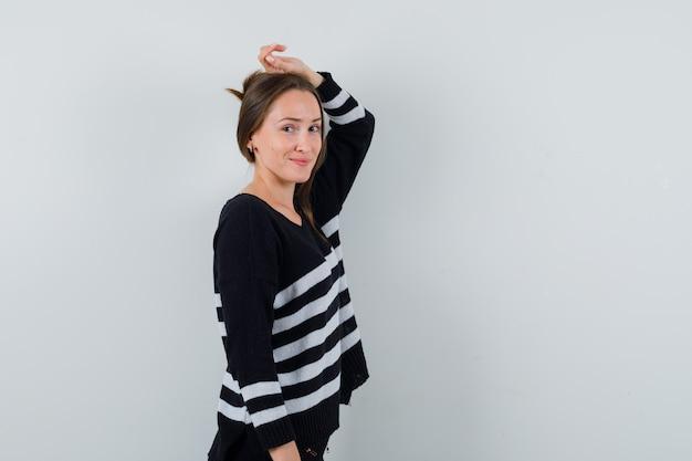 Giovane donna in posa con la mano sulla testa in camicia e dall'aspetto elegante