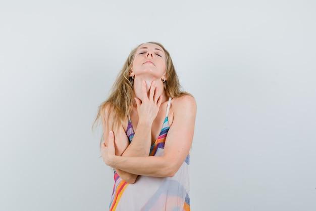 若い女性が夏のドレスに戻って曲がって穏やかなポーズの頭でポーズします。
