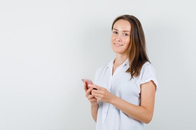 Giovane signora che posa con il telefono in camicetta bianca e sembra bellissima