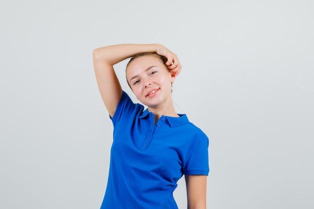 青いtシャツを着て頭に腕を上げてポーズをとって元気に見える若い女性