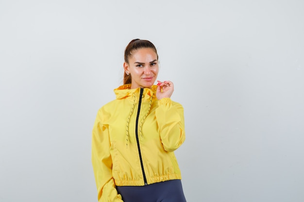 Young lady posing in yellow jacket and looking attractive. front view.