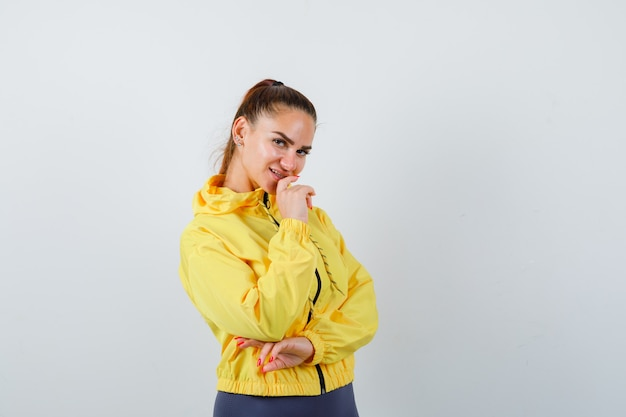 Giovane signora che posa in giacca gialla e sembra allegra. vista frontale.