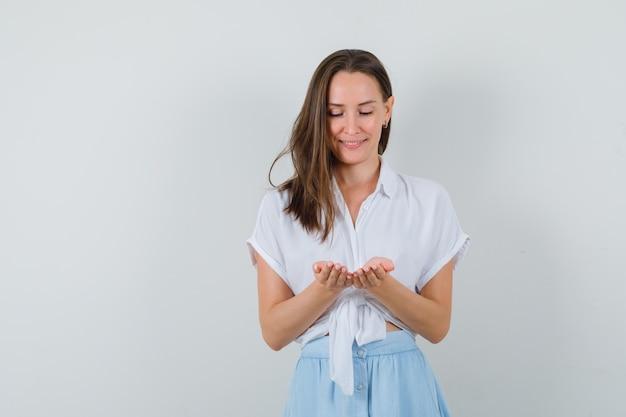 Giovane donna che prega per qualcosa in camicetta e gonna e cerca spazio libero per il tuo testo