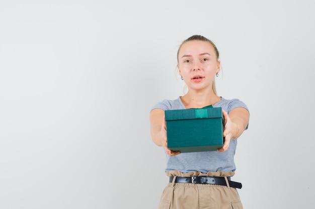T- 셔츠와 바지에 선물 상자를 제시하고 부드러운 찾고 젊은 아가씨