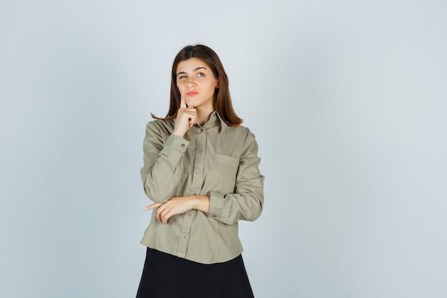 Молодая дама нажимает пальцем на щеку в рубашке, юбке и выглядит задумчиво
