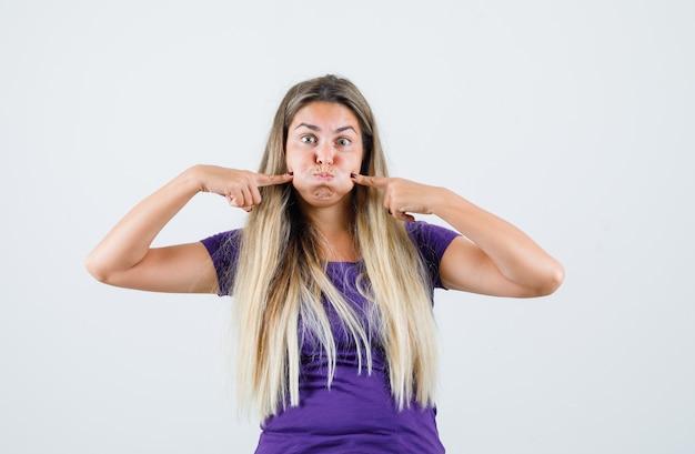 Giovane signora che preme le dita sulle guance soffiate in maglietta viola, vista frontale.