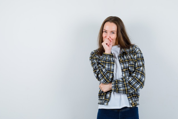 Tシャツ、ジャケットで拳を口に押し付け、楽観的に見える若い女性。正面図。