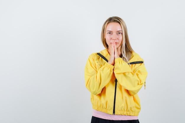 Tシャツ、ジャケット、希望に満ちた表情で手を一緒に押す若い女性