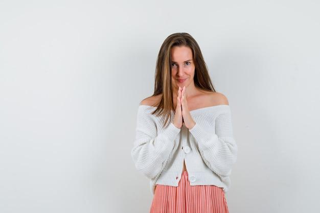 Giovane signora che preme le mani insieme per pregare in cardigan isolato