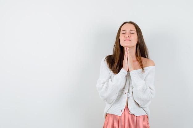 Giovane signora che preme le mani insieme per pregare in cardigan e gonna cercando speranzoso isolato