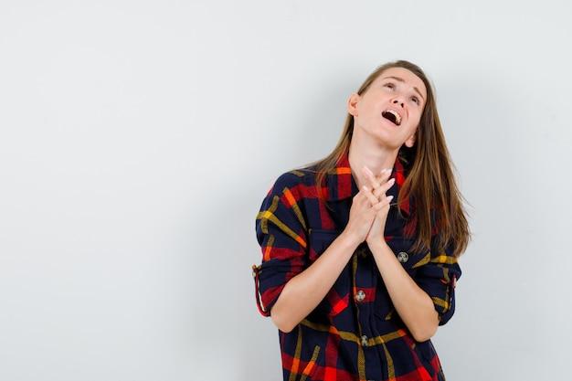 カジュアルなシャツを着て祈っている間、一緒に手を押して、希望に満ちた正面図を探している若い女性。