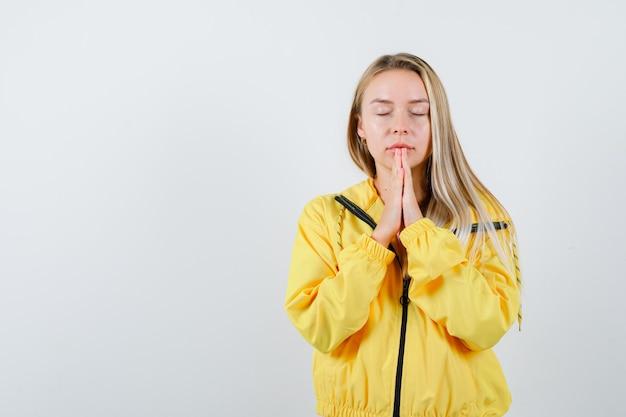 Tシャツ、ジャケットで祈って、平和に見えながら手を一緒に押す若い女性