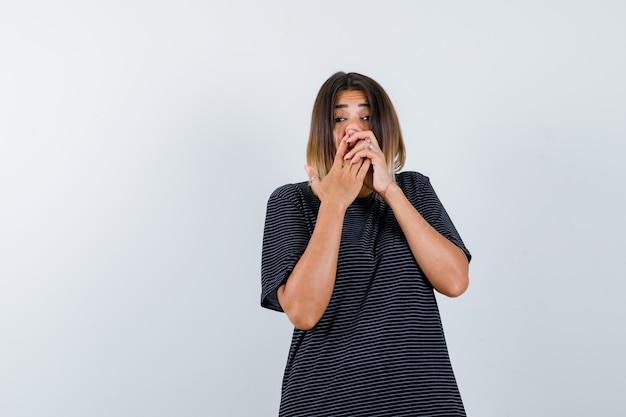 Молодая дама нажимает нос руками в платье-поло и выглядит смешно, вид спереди.