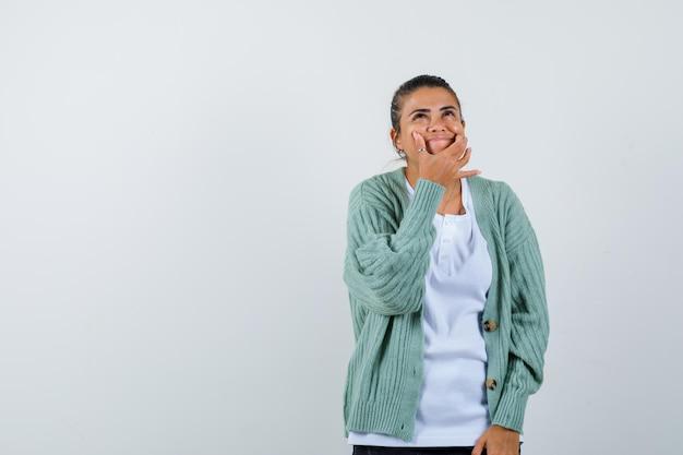 Tシャツ、ジャケット、かわいく見える指で頬を押す若い女性