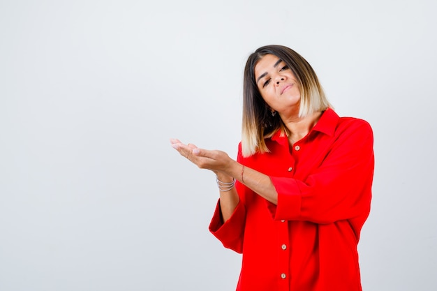 Giovane donna che finge di tenere o mostrare qualcosa in camicia rossa oversize e sembra sicura. vista frontale.