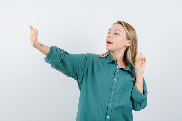 Giovane donna che finge di posare mentre prende selfie in camicia verde e sembra aggraziata