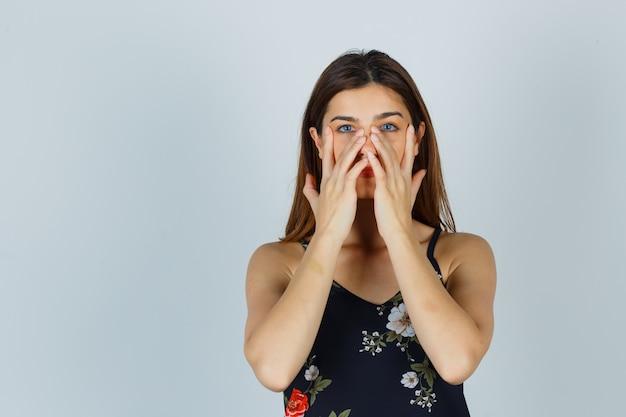 Giovane donna che finge di strofinare la maschera intorno alla zona del naso in camicetta e sembra affascinante. vista frontale.