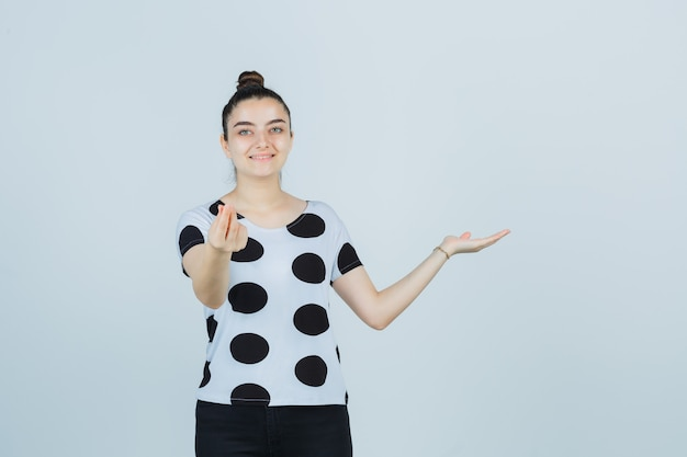Young lady pretending to show something while showing money gesture in t-shirt, jeans and looking joyful , front view.