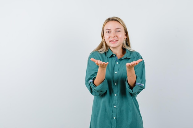 녹색 셔츠에 무언가를 쥐거나 제공하는 척하고 귀엽게 보이는 젊은 아가씨