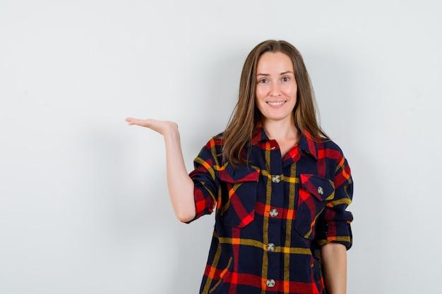 カジュアルなシャツを着て何かを見せているふりをして陽気に見えるお嬢様、正面図。