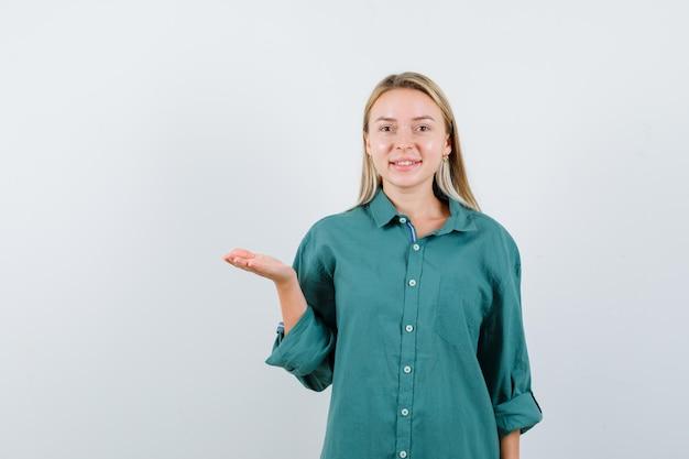 緑のシャツを着て何かを見せているふりをして元気そうな若い女性。