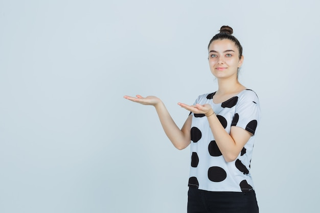 Tシャツ、ジーンズ、自信を持って、正面から何かを見せているふりをしている若い女性。