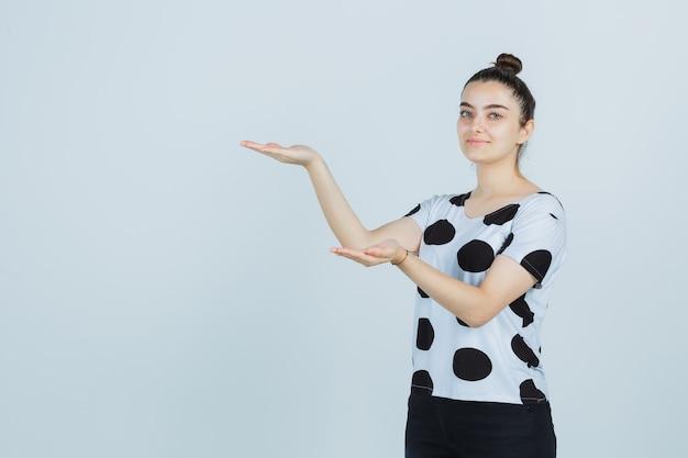 Молодая дама делает вид, что показывает что-то в футболке, джинсах и выглядит уверенно, вид спереди.
