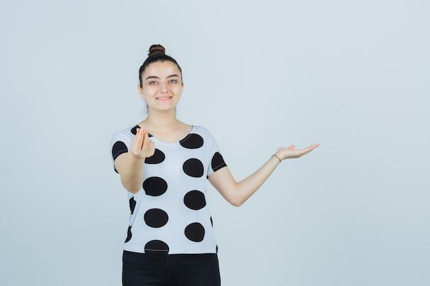 Девушка делает вид, что показывает что-то, показывая денежный жест в футболке, джинсах и радостно, вид спереди.