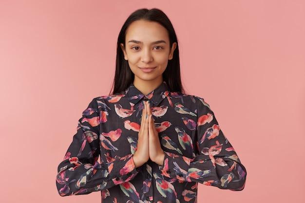 Giovane donna, donna piuttosto asiatica con i capelli lunghi scuri, indossa una camicia nera con uccelli