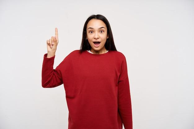 Signora giovane, donna abbastanza asiatica con capelli lunghi scuri. indossa un maglione rosso e indica lo spazio della copia. alza il dito indice, mi è venuta un'idea. guardando la telecamera isolata su sfondo bianco