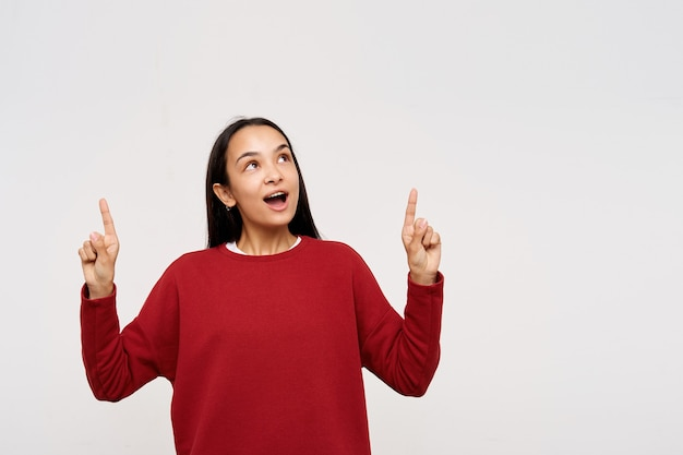Young lady, pretty asian woman with dark long hair. wearing red sweater and pointing up in wonder of what she see. watching up at copy space, isolated, over white background