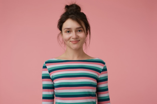 Signora giovane, donna graziosa del brunette con il panino. indossa una camicetta a righe e ha un sorriso carino, felice di vederti, mostrando sicurezza. isolato su muro rosa pastello