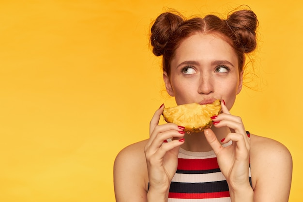 Young lady, pretty ginger woman with two buns and healthy skin. wearing striped tank top and biting slice of a pineapple. watching to the left at copy space, isolated closeup over yellow wall