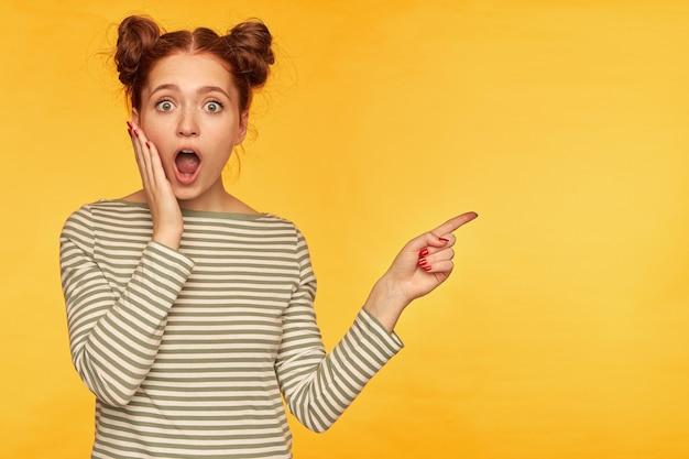 젊은 아가씨, 두 개의 빵을 가진 예쁜 생강 여자. 그녀의 뺨을 만지고 충격을 받았다. 줄무늬 스웨터를 입고 노란색 벽 위에 복사 공간에서 오른쪽을 가리키는