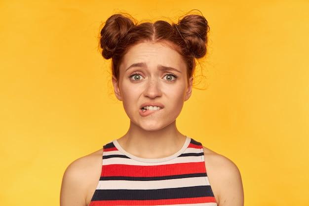 Giovane donna, graziosa donna rossa con due panini. indossa una maglietta a righe e si morde il labbro. sembra preoccupato, impaurito. guardando, primo piano, isolato sopra la parete gialla