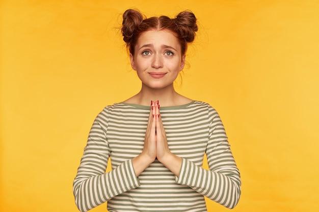 젊은 아가씨, 두 개의 빵을 가진 예쁜 생강 여자. 줄무늬 스웨터를 입고 기뻐하고 있습니다. 도움을 요청하고, 용서를 구하고, 손바닥을 함께 유지합니다. 노란색 벽 위에 절연 스탠드