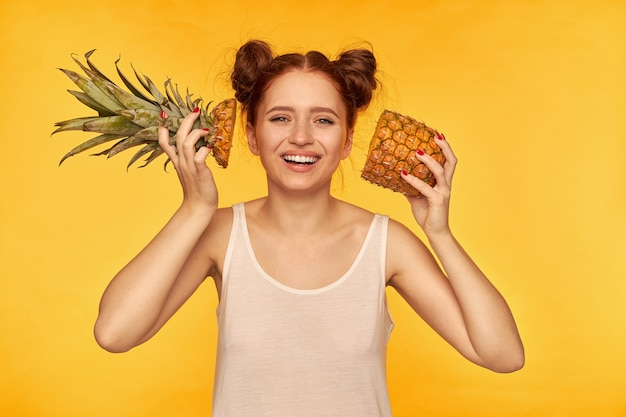 若い女性、2つのパンを持つかなり生姜の女性。白いシャツを着て、カットパイナップルを顔の横に持って、笑顔で健康的なライフスタイルを。黄色い壁越しに孤立して見ている
