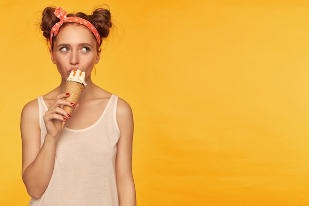 Young lady, pretty ginger woman with two buns. wearing white tank top and red doted hairband. eating an ice cream. watching to the right at copy space, isolated over yellow wall