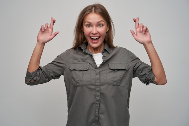 Young lady, pretty woman with brown long hair. wearing grey shirt and crossed her fingers. cheerful, making a wish. smiling. watching at the camera isolated over grey background